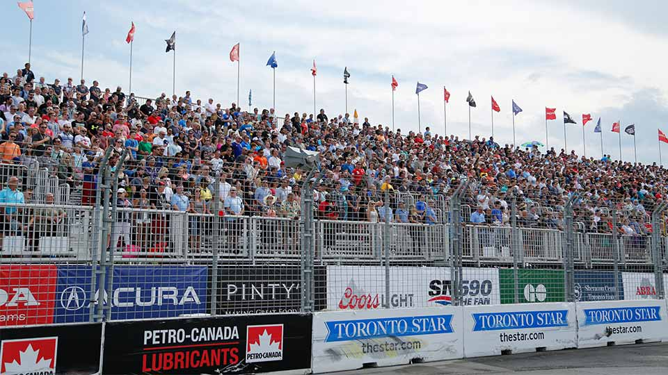 A crowded grandstand at the Honda Indy Toronto atop sponsor signage